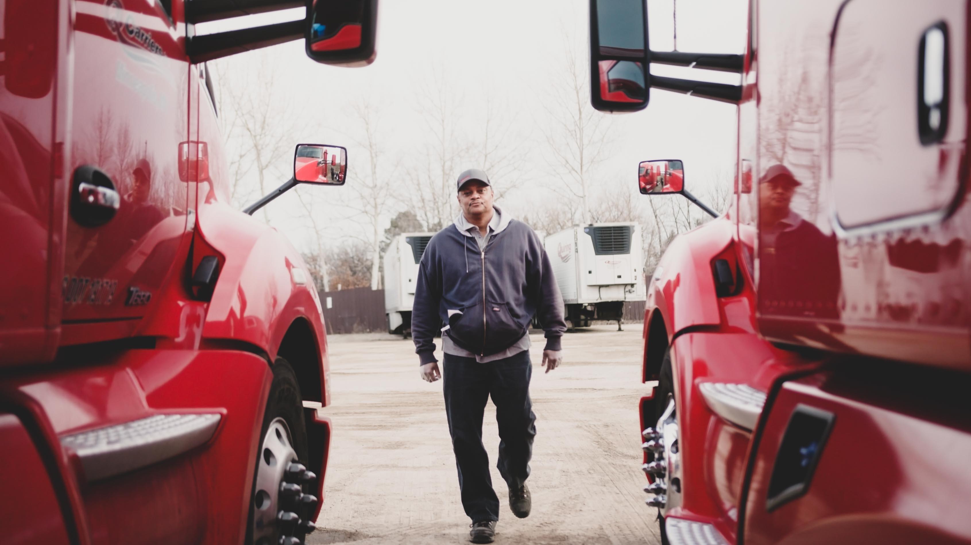 man standing between two red trucks