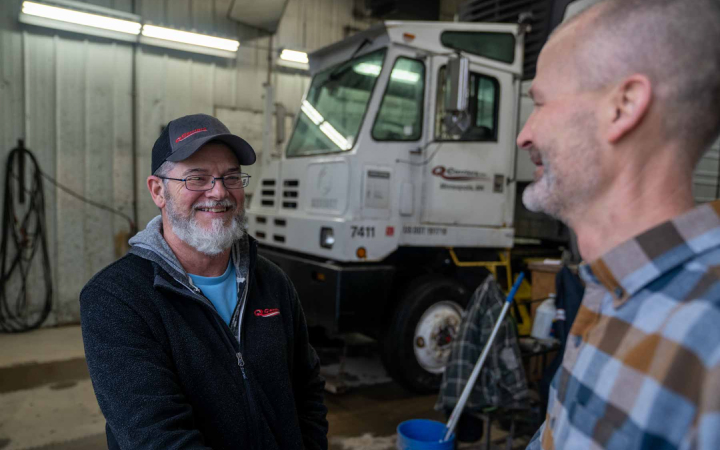 men shaking hands in front of a truck