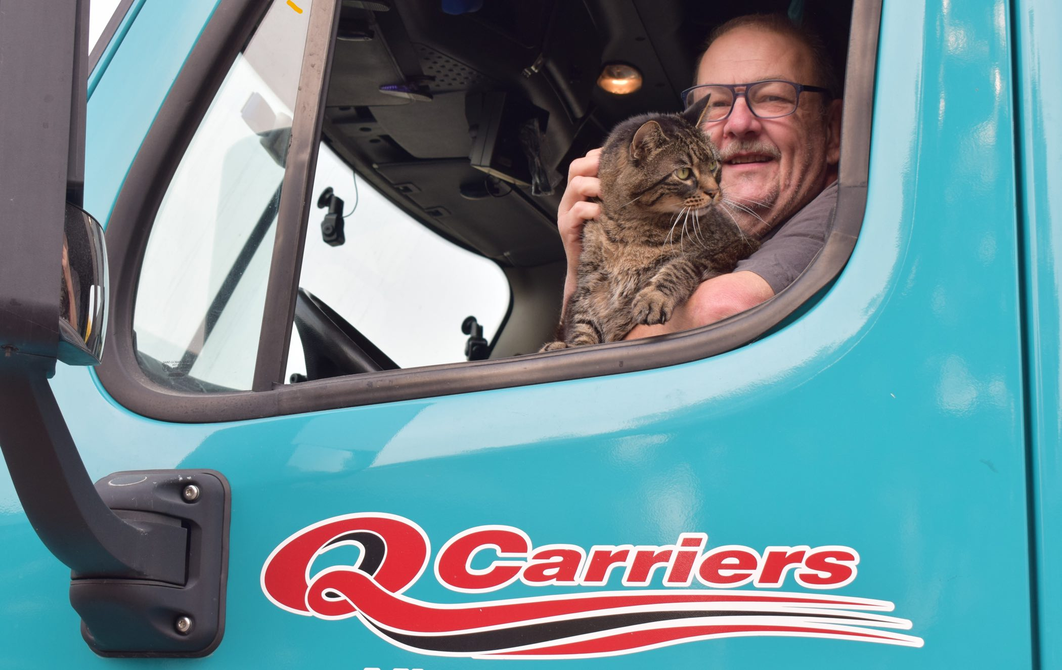 man holding his cat inside a truck