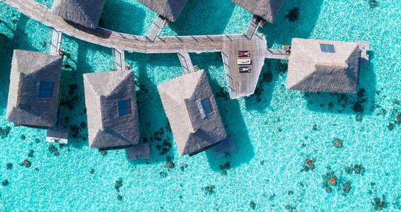 Top aerial view of the overwater bungalows surrounding crystal clear turquoise waters of Bora Bora.