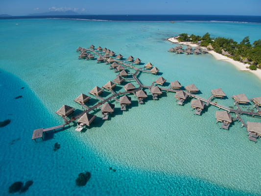 A complete aerial view of the beautiful overwater bungalows of InterContinental Bora Bora Le Moana surrounded by crystal clear turquoise waters.