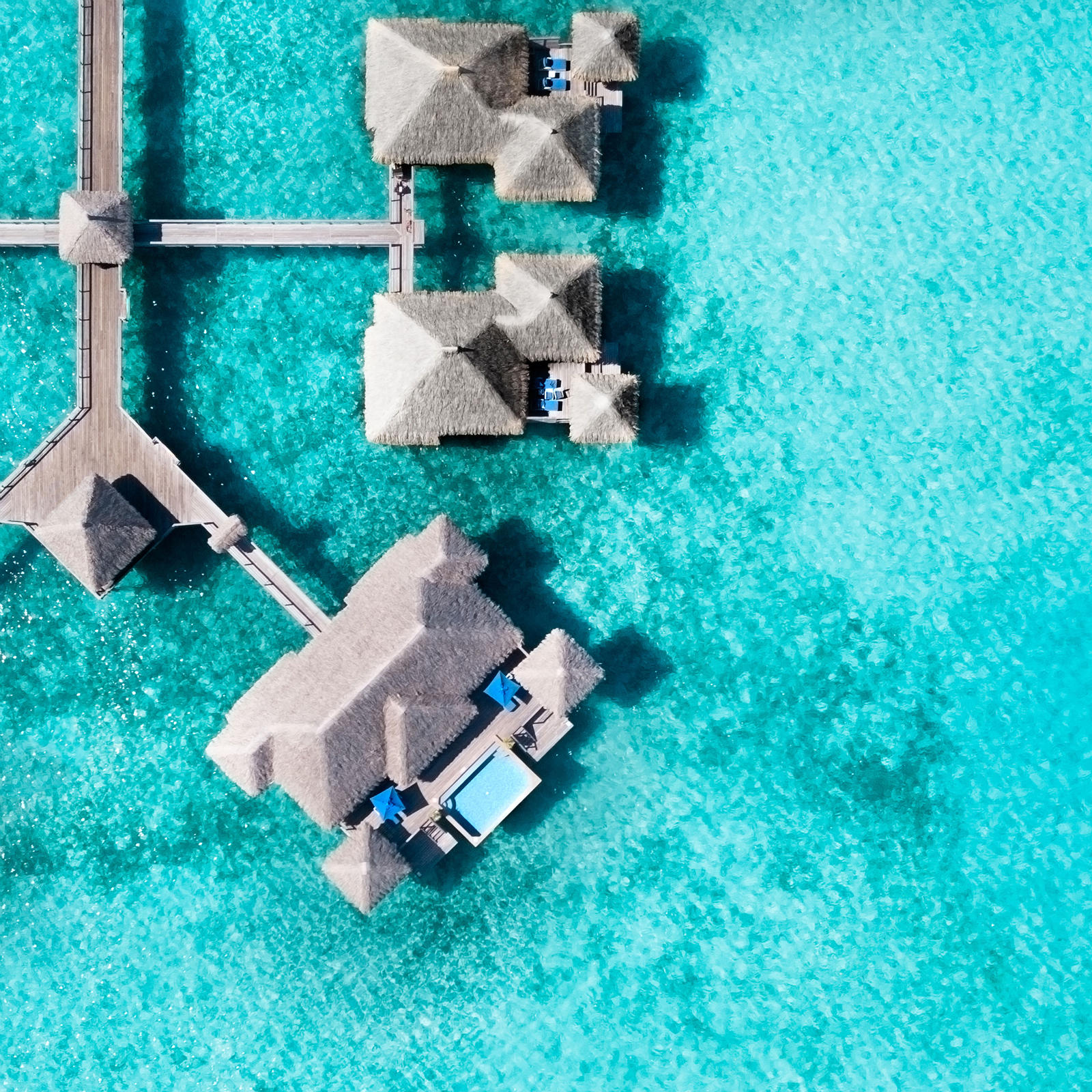 Aerial view of The St. Regis Bora Bora Resort's Overwater Villas & Pool Villas atop a turquoise lagoon with remarkable clarity.