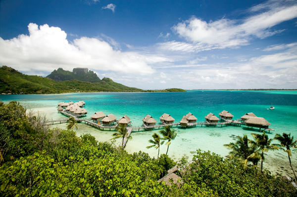 Exquisite view of the beautiful overwater bungalows on the crystal clear water of the lagoon with the Majestic Mt. Otemanu on the horizon.