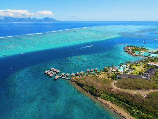 Aerial view of the InterContinental Tahiti Resort surrounded by clear blue waters and nearby islands on the horizon.
