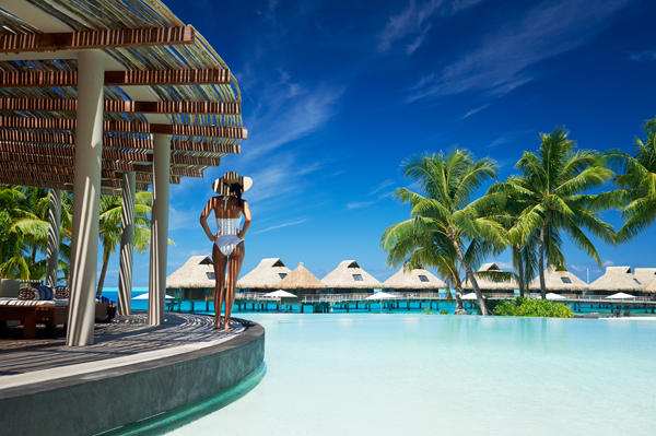 A Girl on white swimwear standing by the pool admiring the beautiful overwater bungalows in the distance under the Tahitian sun.