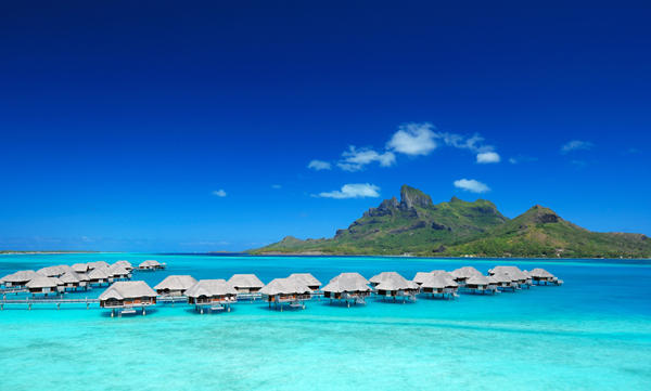 A complete view of the beautiful overwater bungalows surrounded by crystal clear blue waters and the majestic Mt. Otemanu.
