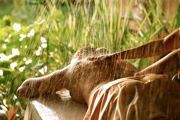 A lady enjoying rain-like massage at Tavai Spa of Le Tahaa by Pearl Resorts.