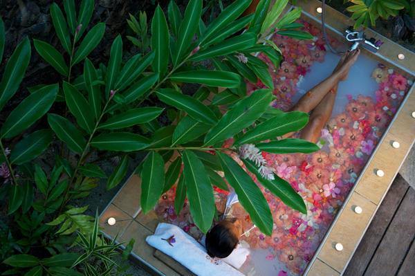 Girl enjoying a flower bath soak on a pool beach villa of Le Tahaa by Pearl Resorts.