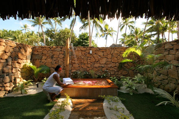 Resort personnel preparing the outdoor bath of the pool beach villa with flowers.