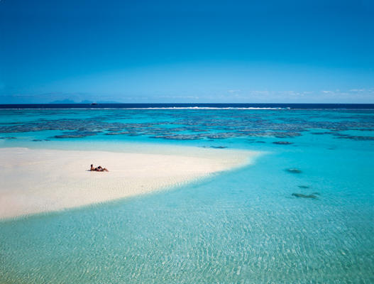 Honeymoon Couple lounging on the private white sandbar surrounded by crystal clear waters of The Brando Resort in Tetiaroa.