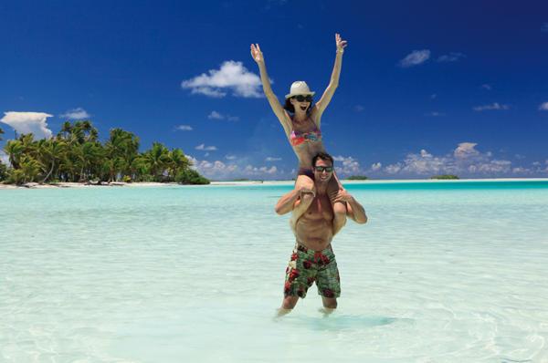 Sweet Honeymoon couple enjoying the gorgeous tahitian sun playing on the shallow crystal blue waters of Rangiroa Island at French Polynesia.