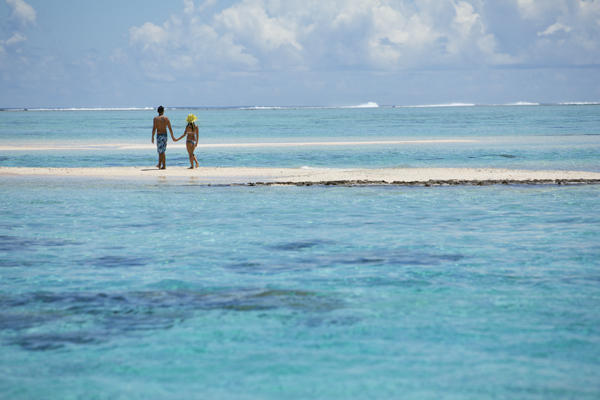 Romantic honeymoon couple enjoying a private sandbar under the tahitian sun surrounded by crystal blue waters.