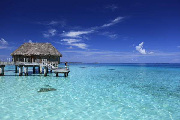 Romantic honeymoon couple on a deck of an overwater bungalow overlooking the crystal blue waters of a Bora Bora Lagoon.
