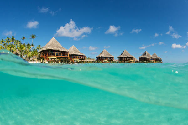 A glimpse of the beautiful overwater bungalows from the crystal turquoise waters under clear blue skies.