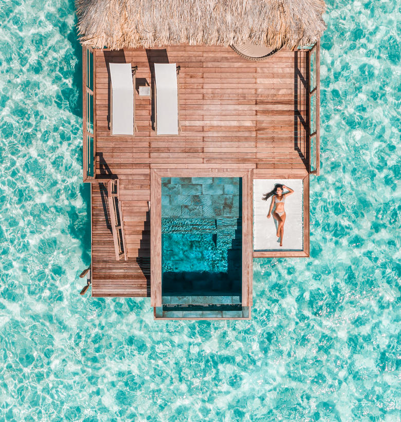 Guest in bikini lounging on the deck of a Pool Overwater Villa at Le Bora Bora by Pearl Resorts atop crystal clear aqua water.