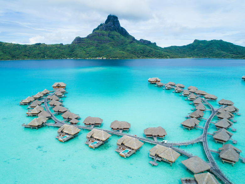 Aerial view of overwater bungalows at the Intercontinental Bora Bora & Thalasso Spa with Mt. Otemanu in the distance.