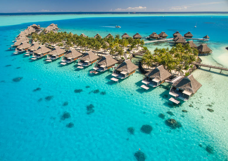 Aerial view of The Conrad Bora Bora Nui's beautiful overwater bungalows surrounded by blue waters with palm trees nearby.