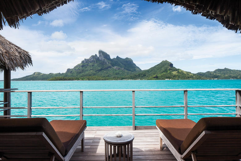 Pristine view from the deck of overwater bungalow at Four Seasons with lounge chairs and a majestic view of Mt. Otemanu.