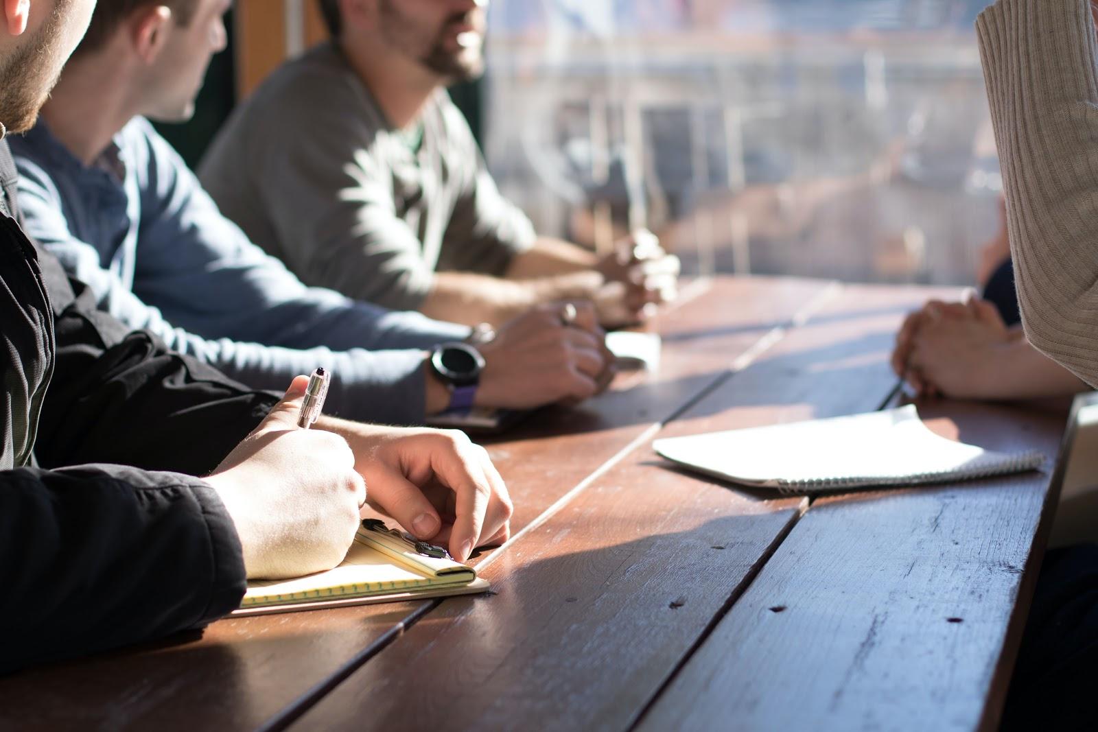 Groupe de collègues au bureau assis autour d'une table gros plan qui coupe leurs visages