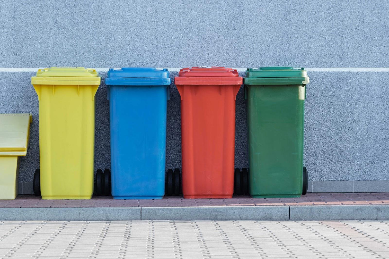 Quatre poubelles pour le recyclage de différentes couleur : jaune, rouge, bleue, verte