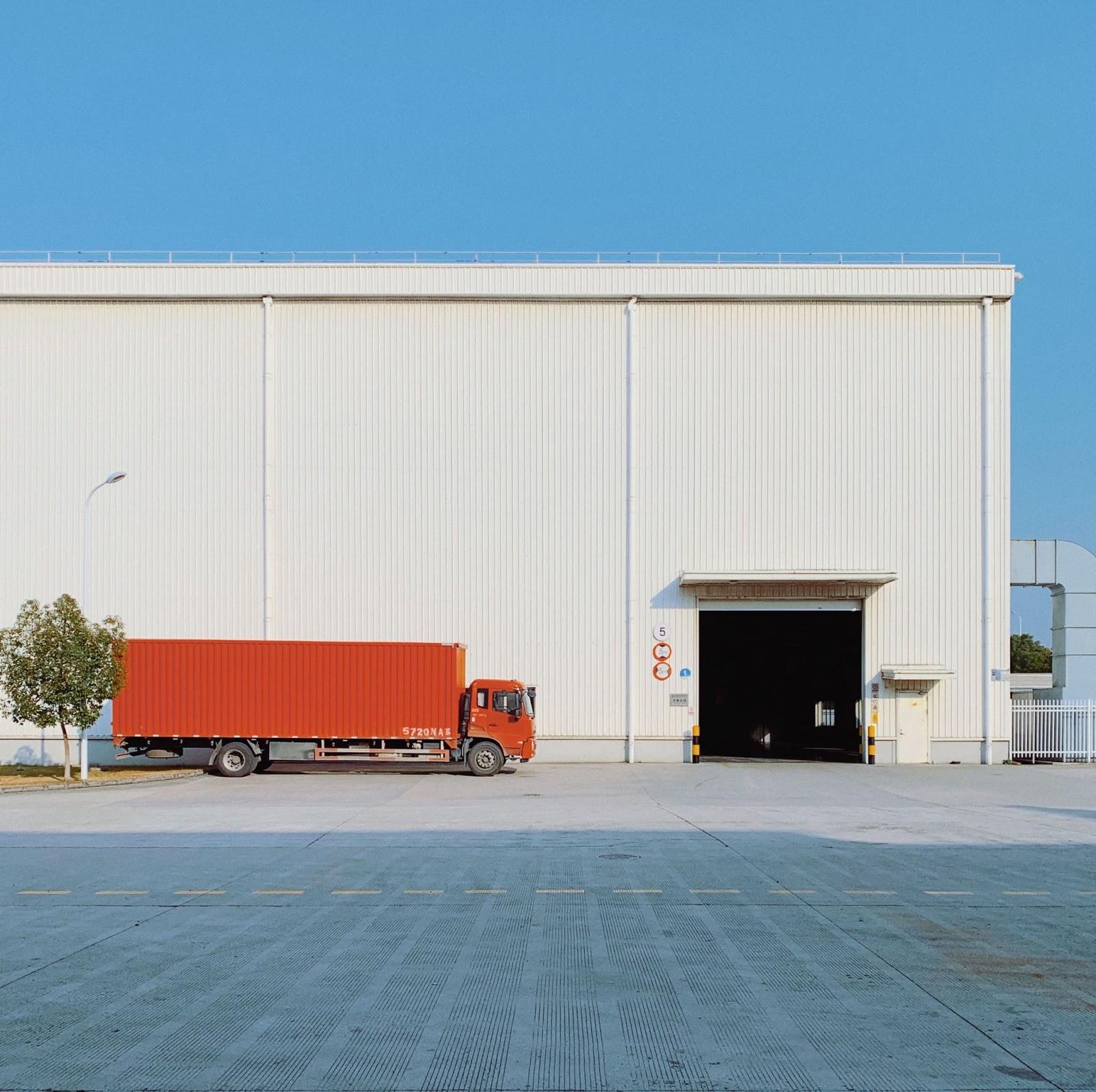 Camion rouge devant un entrepôt et un grand ciel bleu