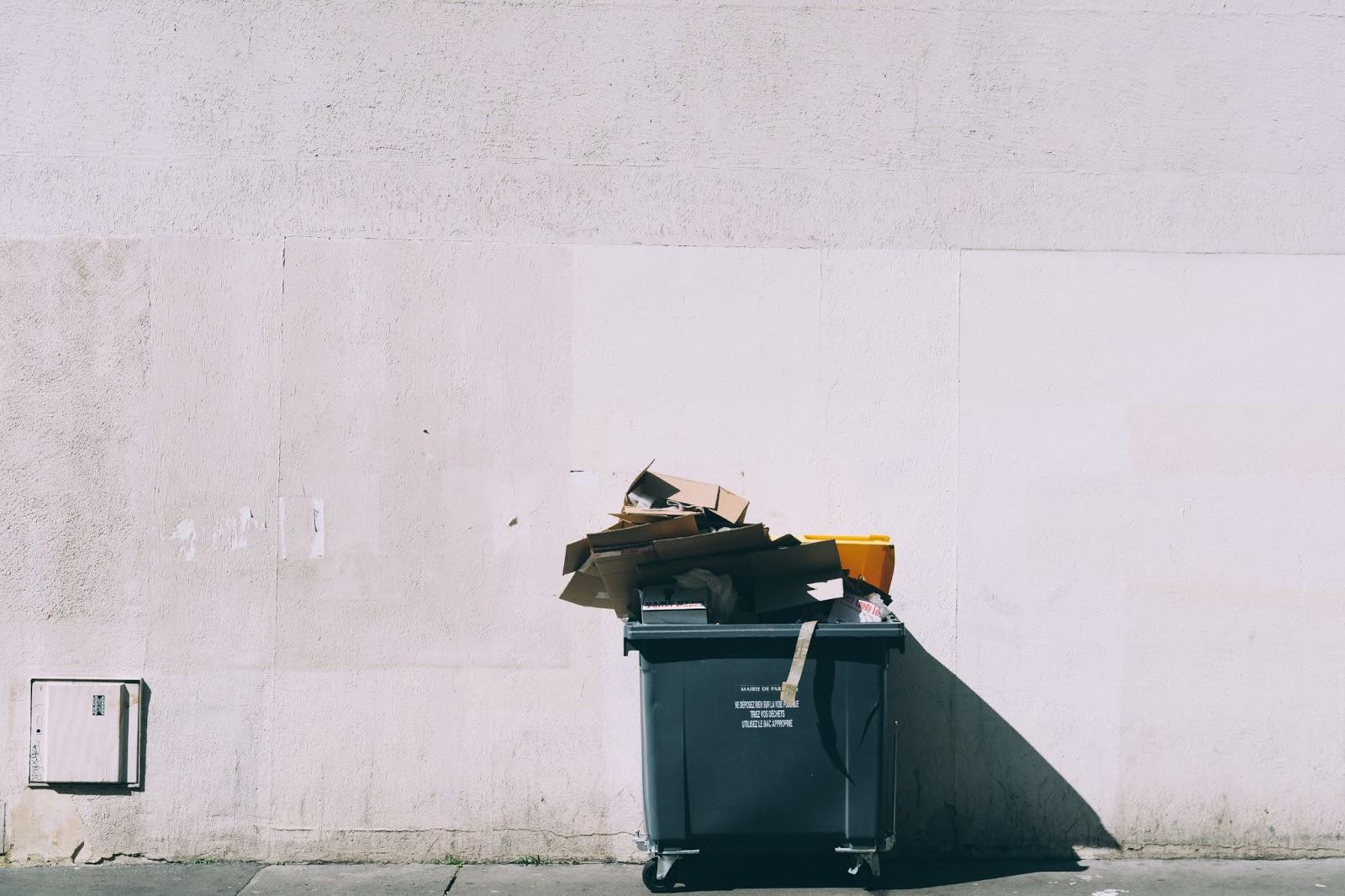 Poubelle débordant de cartons à recycler devant un mur blanc.