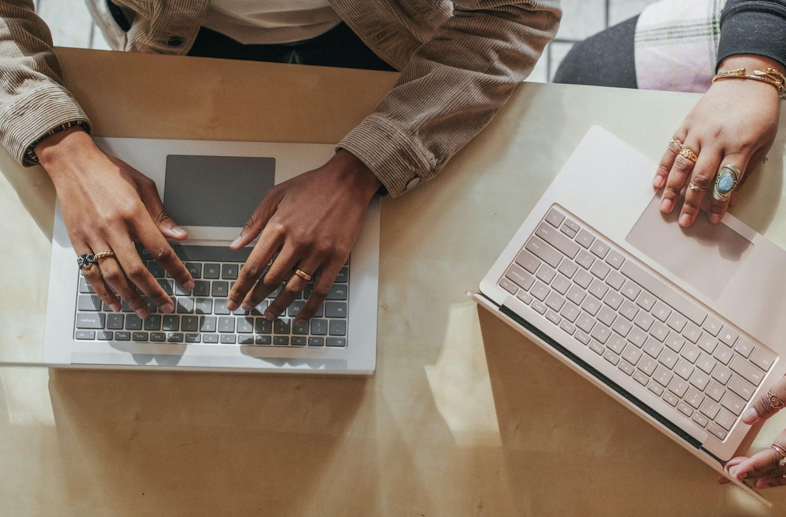 Deux ordinateurs et paires de mains vue du dessus