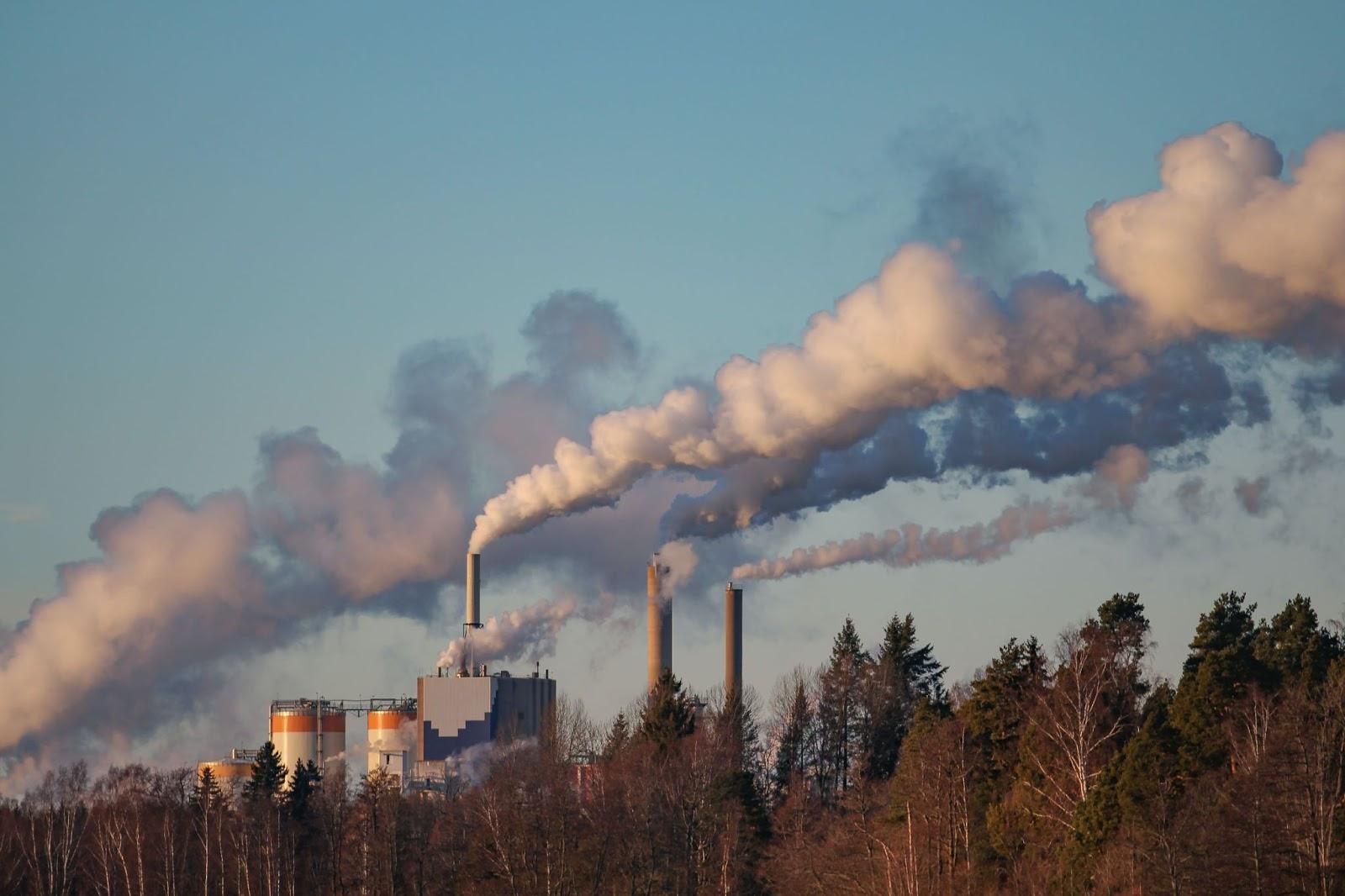 Plusieurs cheminées d'usines qui émettent des nuages blancs de gaz à effet de serre