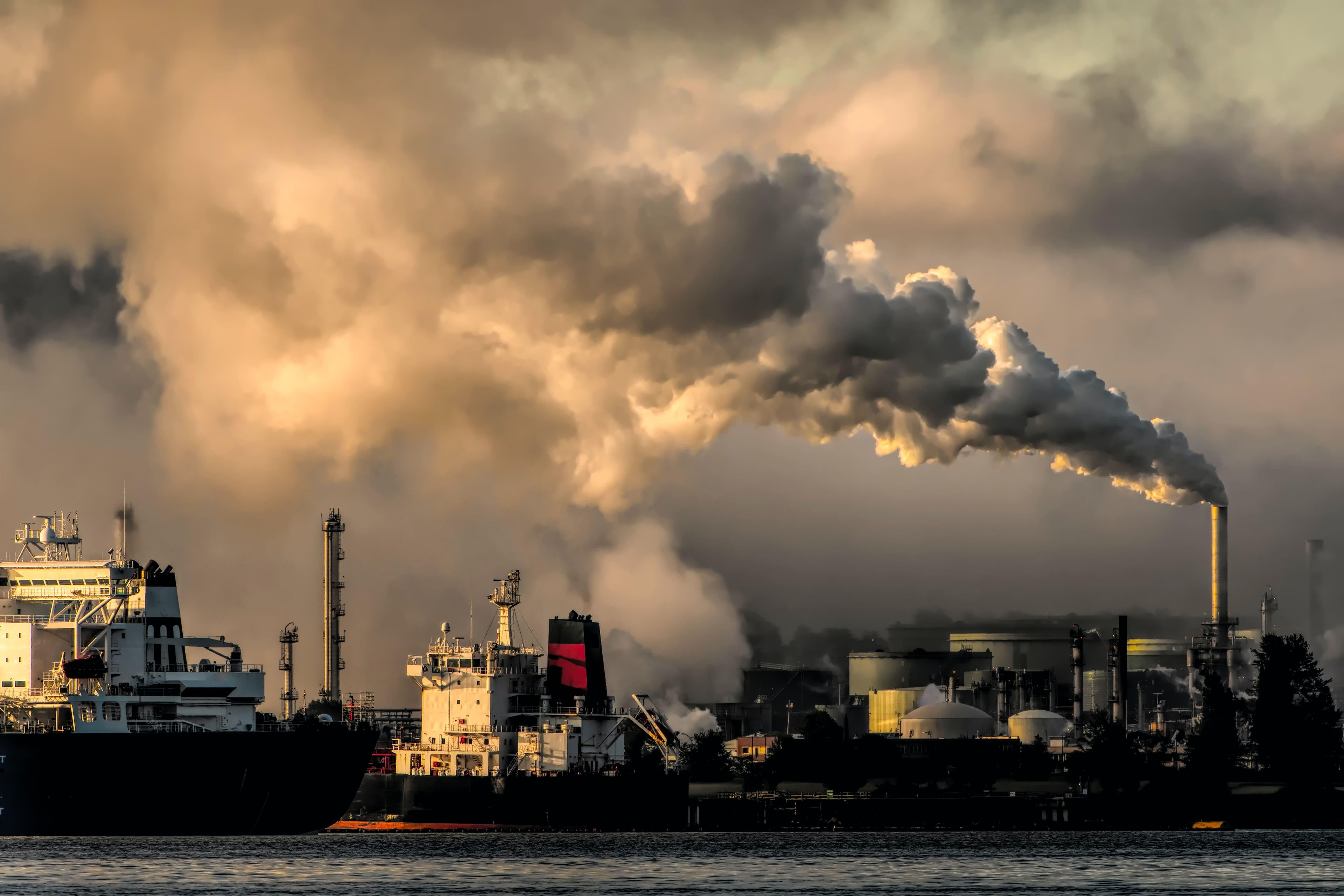 Exploitation de l'industrie pétrolière en train d'extraire des ressources avec de gros nuages polluants au dessus d'eux.