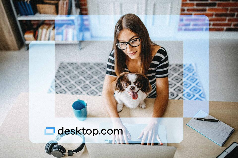 Woman works in front of computer with a dog in her lap with the desktop.com logo super imposed in front