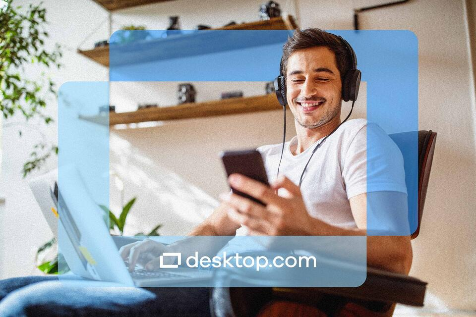 Man smiles while looking at his phone with the desktop.com logo super imposed in the front