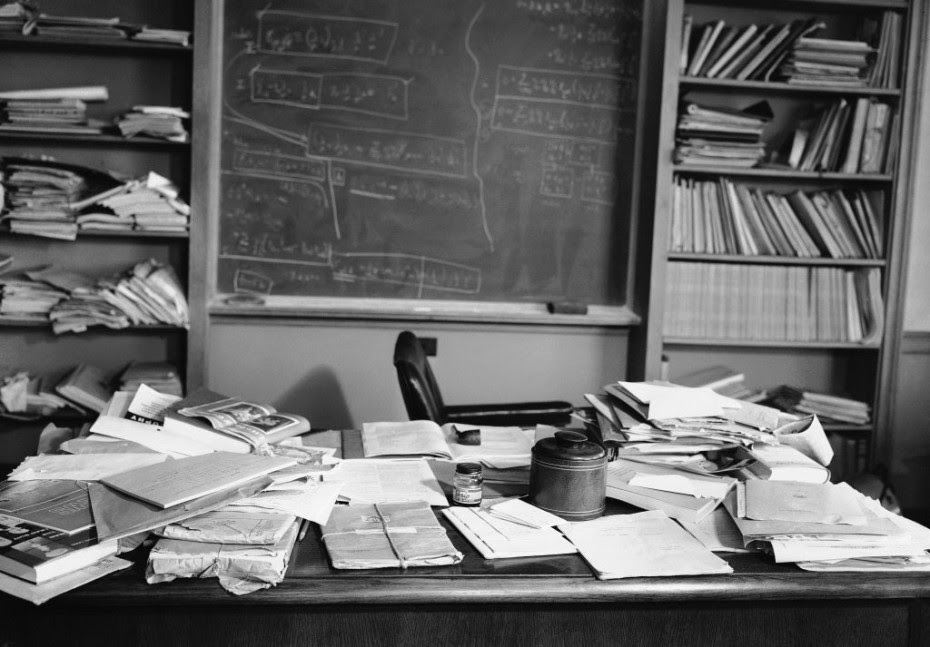 A desk with a lot of clutter and a blackboard in the background