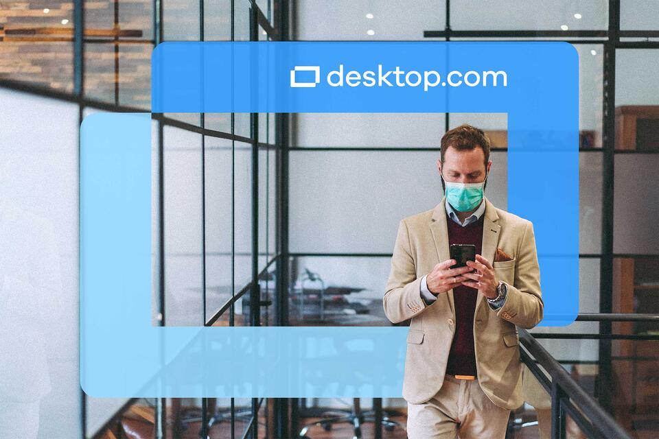Man with facemask looks at phone in an office space