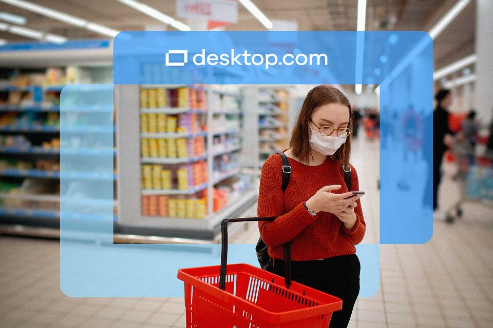Woman with facemask looks at phone at a supermarket