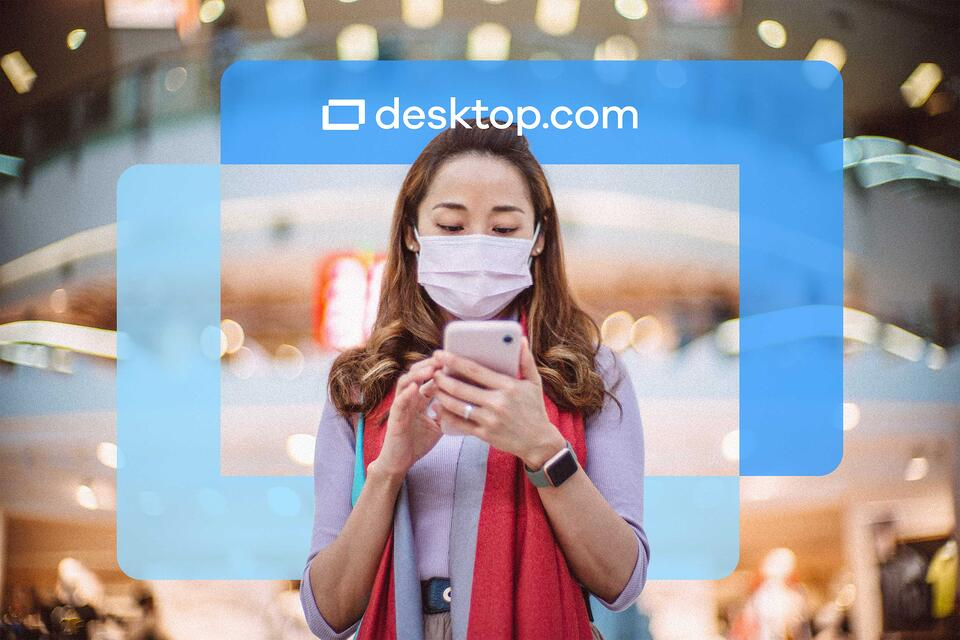 Woman with facemask looks at phone with the desktop.com logo superimposed in front.