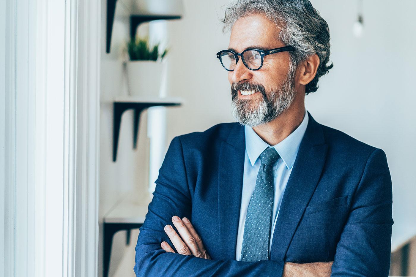 Photo d'un homme d'affaires regardant par la fenêtre, souriant.