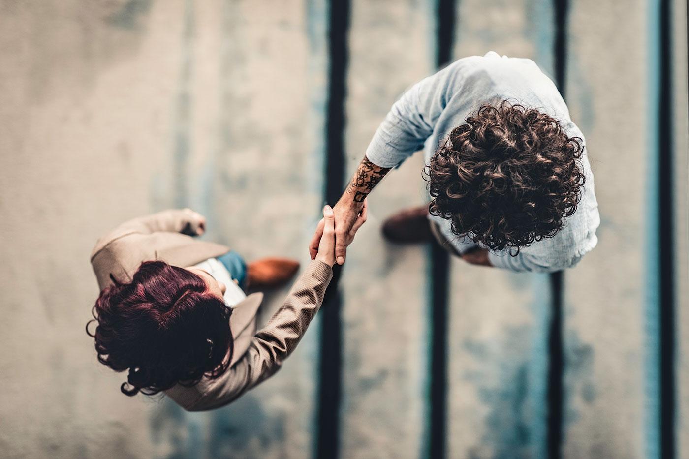 Vu d'en haut, un homme et une femme se serrant la main.