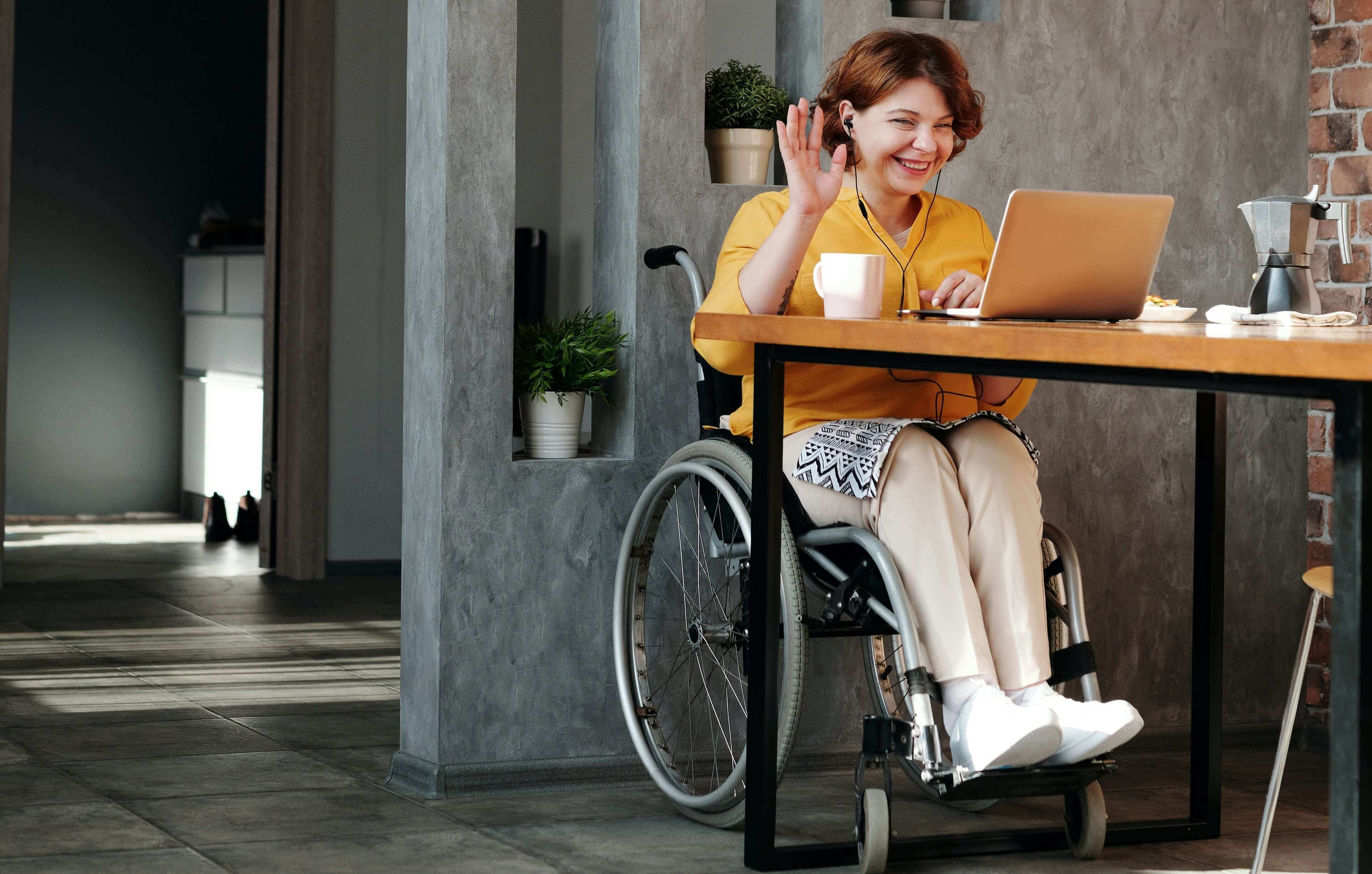 woman in wheelchair smiling and waving into video
