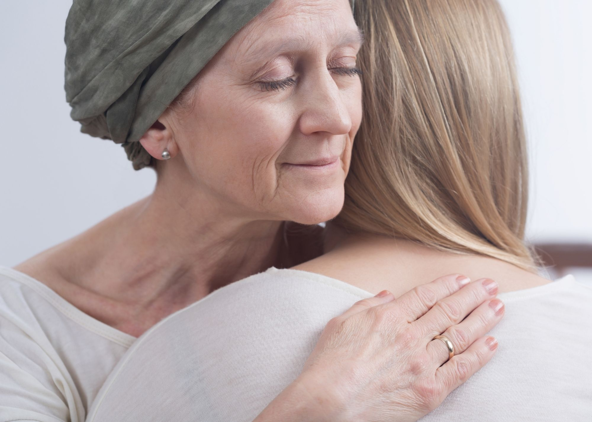 young woman hugging ill older woman