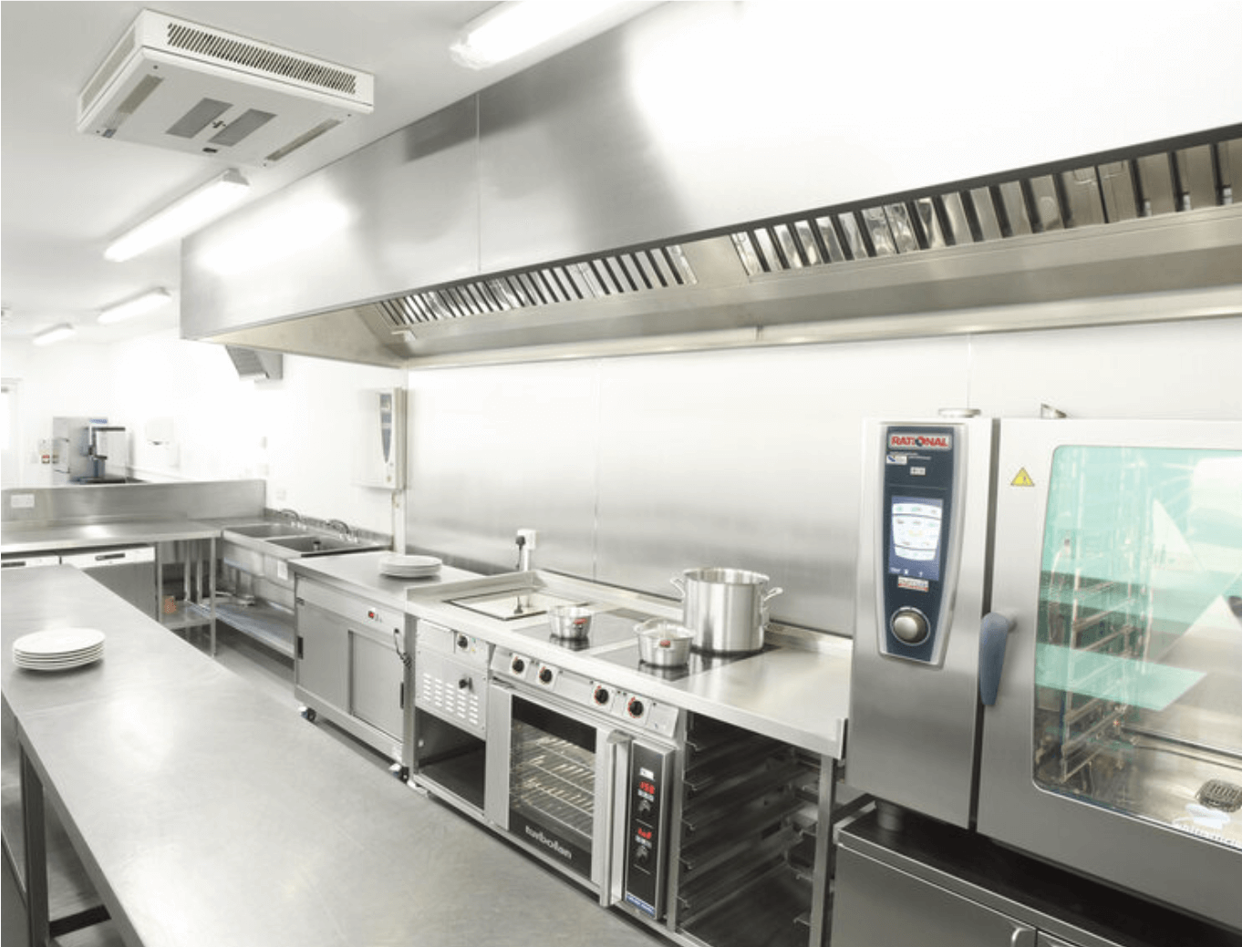 clean commercial kitchen with a professional oven and stainless steel surfaces