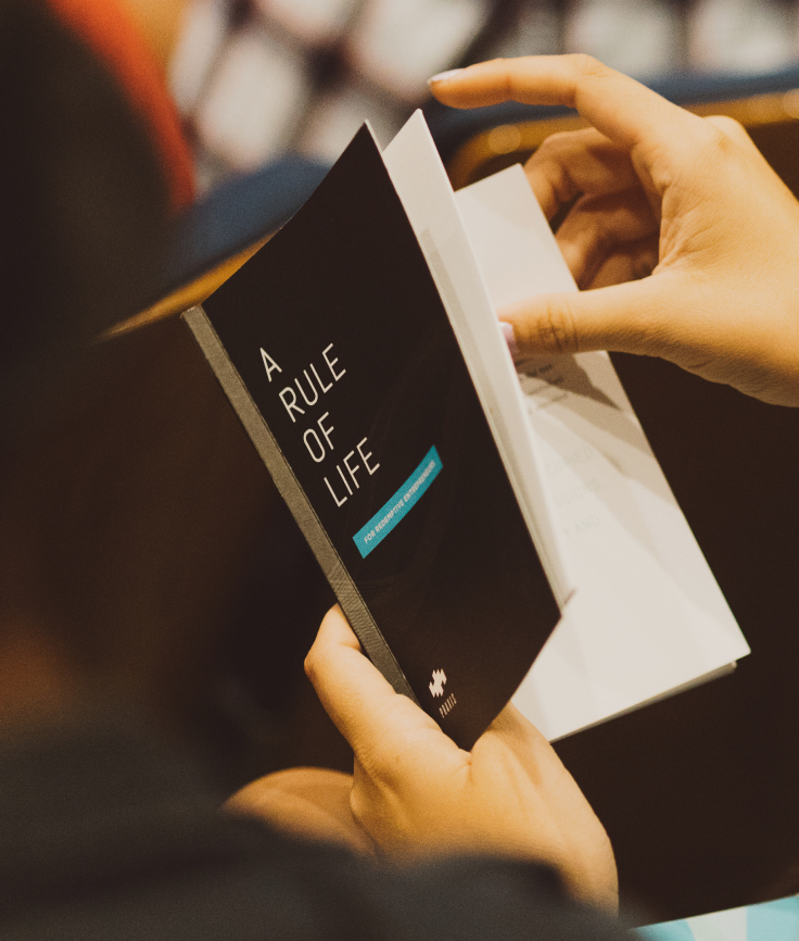 """Close-up of a person flipping through the book, """"A Rule of Life"""""""