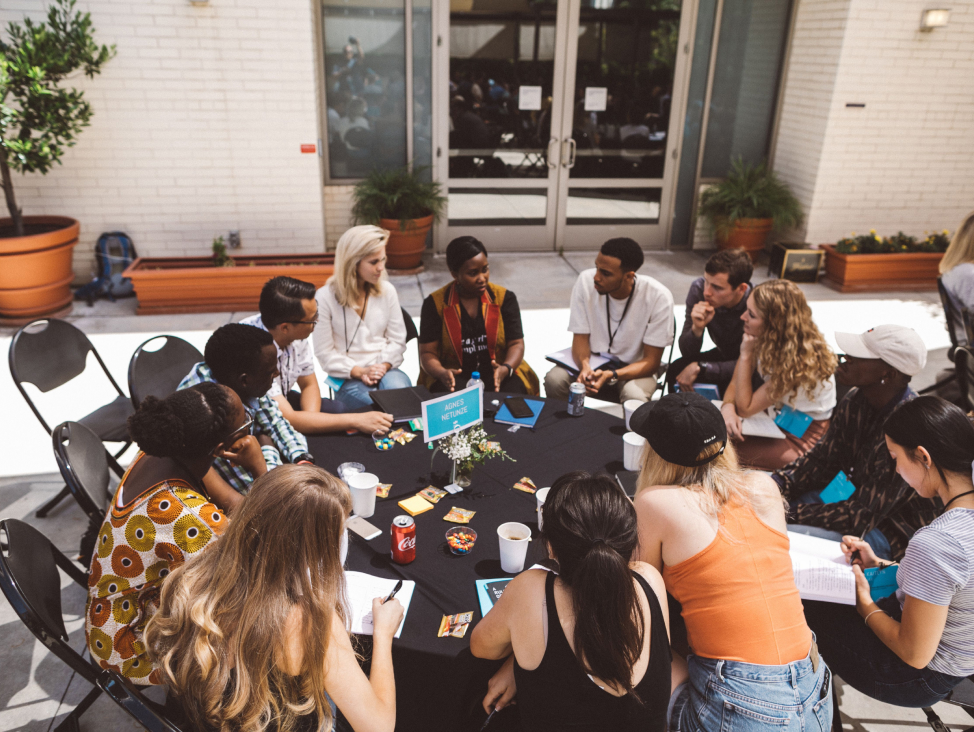 Praxis   a team sitting in a circle having a discussion.