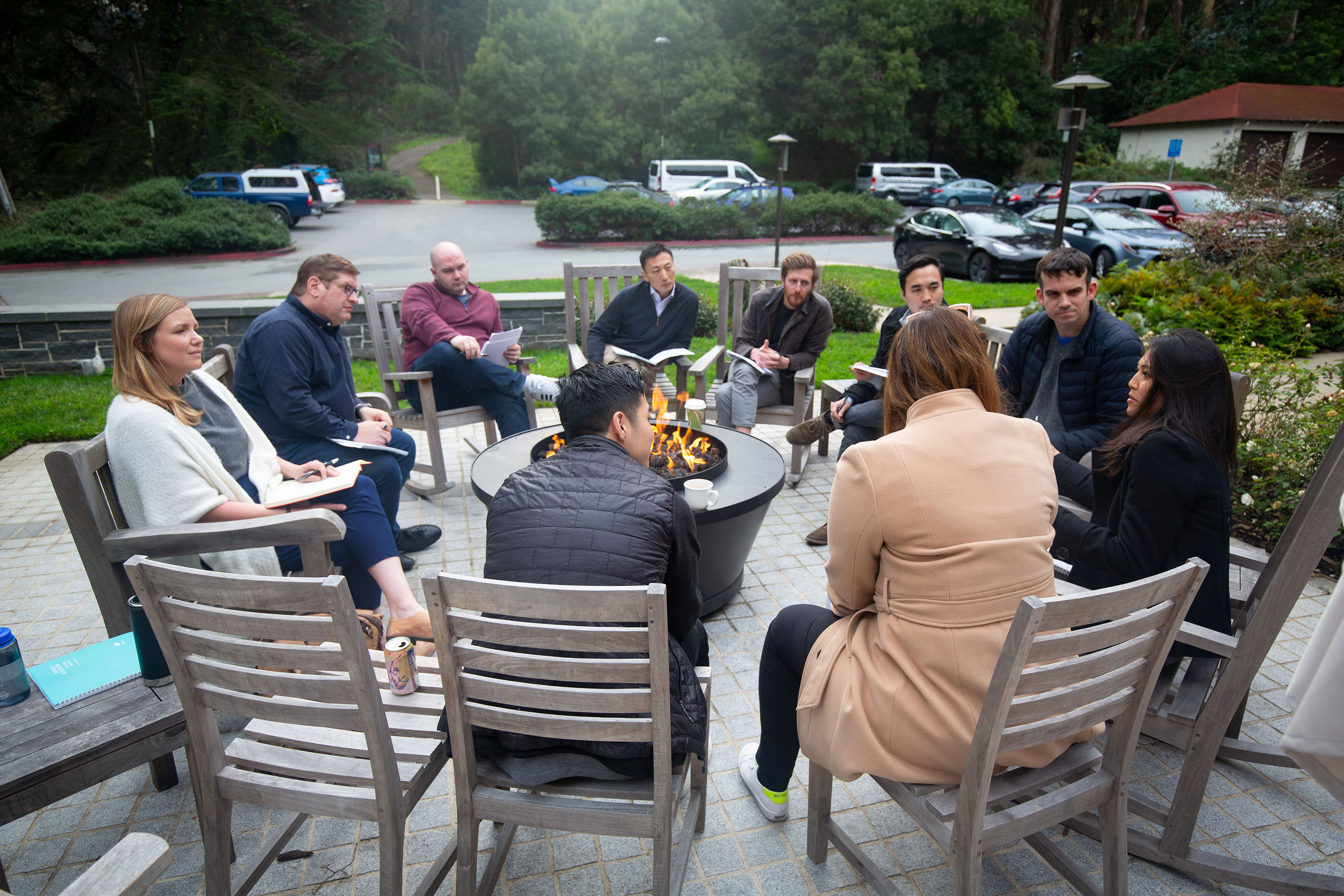 A group of Praxis fellows engaged in discussion seated in a circle around a fire pit.