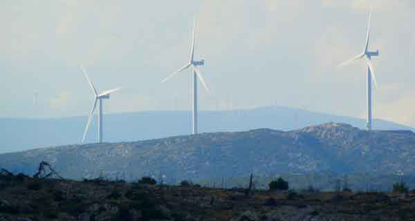 A windfarm in the distance on a hill depicting ESG criteria.