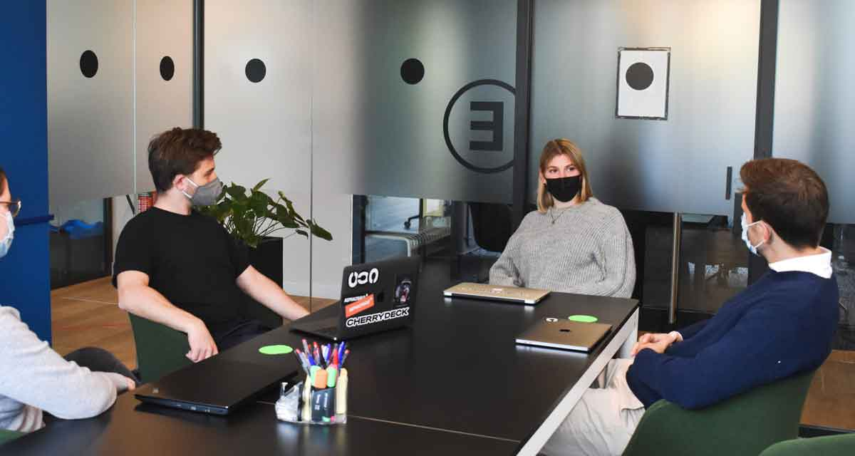 A group with Covid masks discussing business consistency