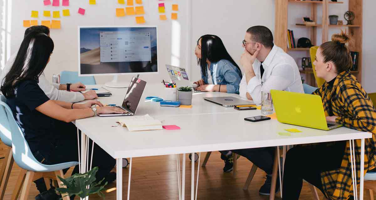 employees around desk collaborating on work