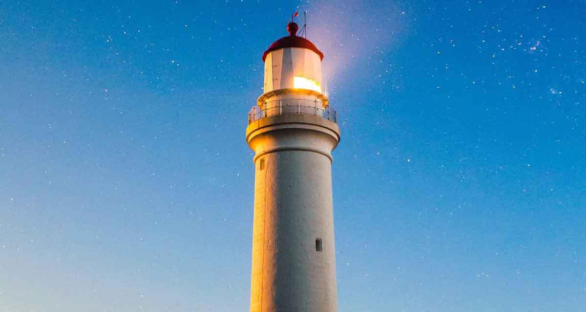 lighthouse lighting up the sky