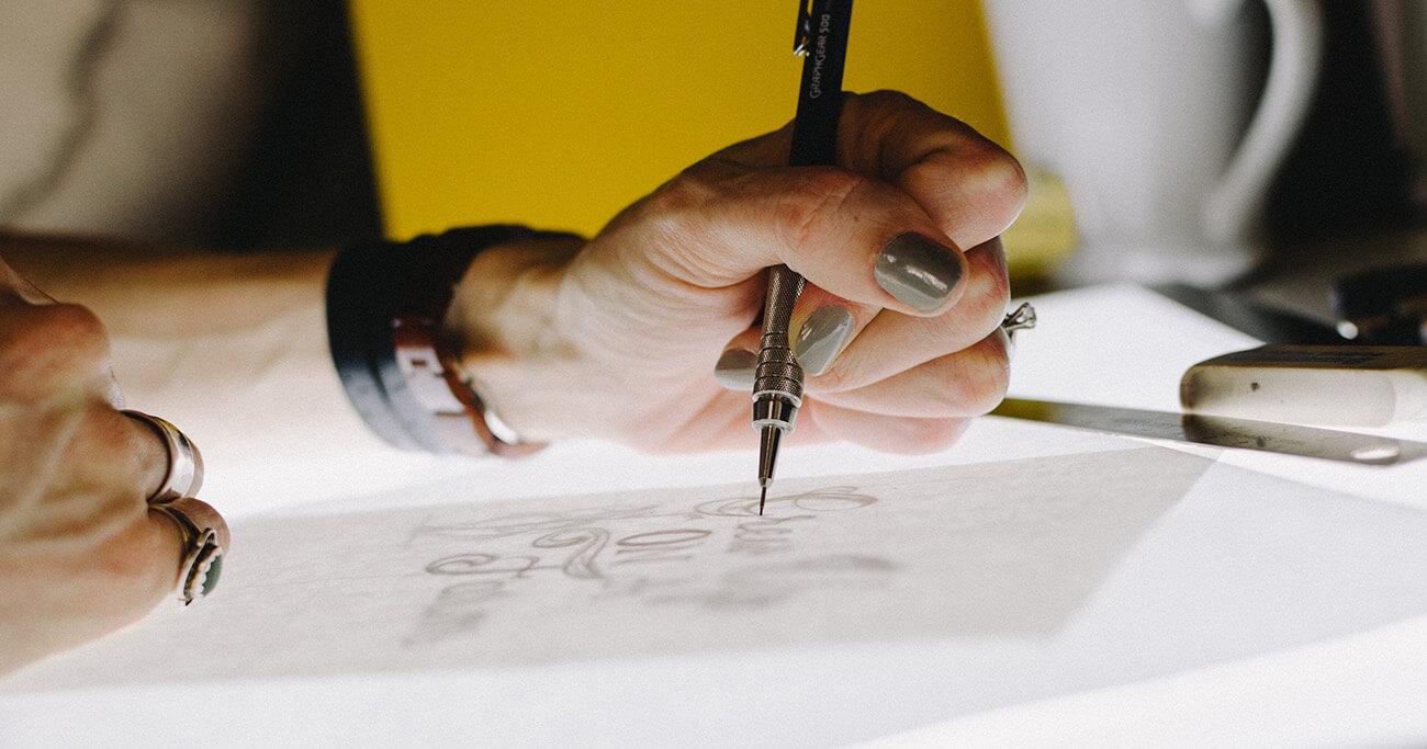 Hand mit Stift zeichnet auf Zeichenbrett