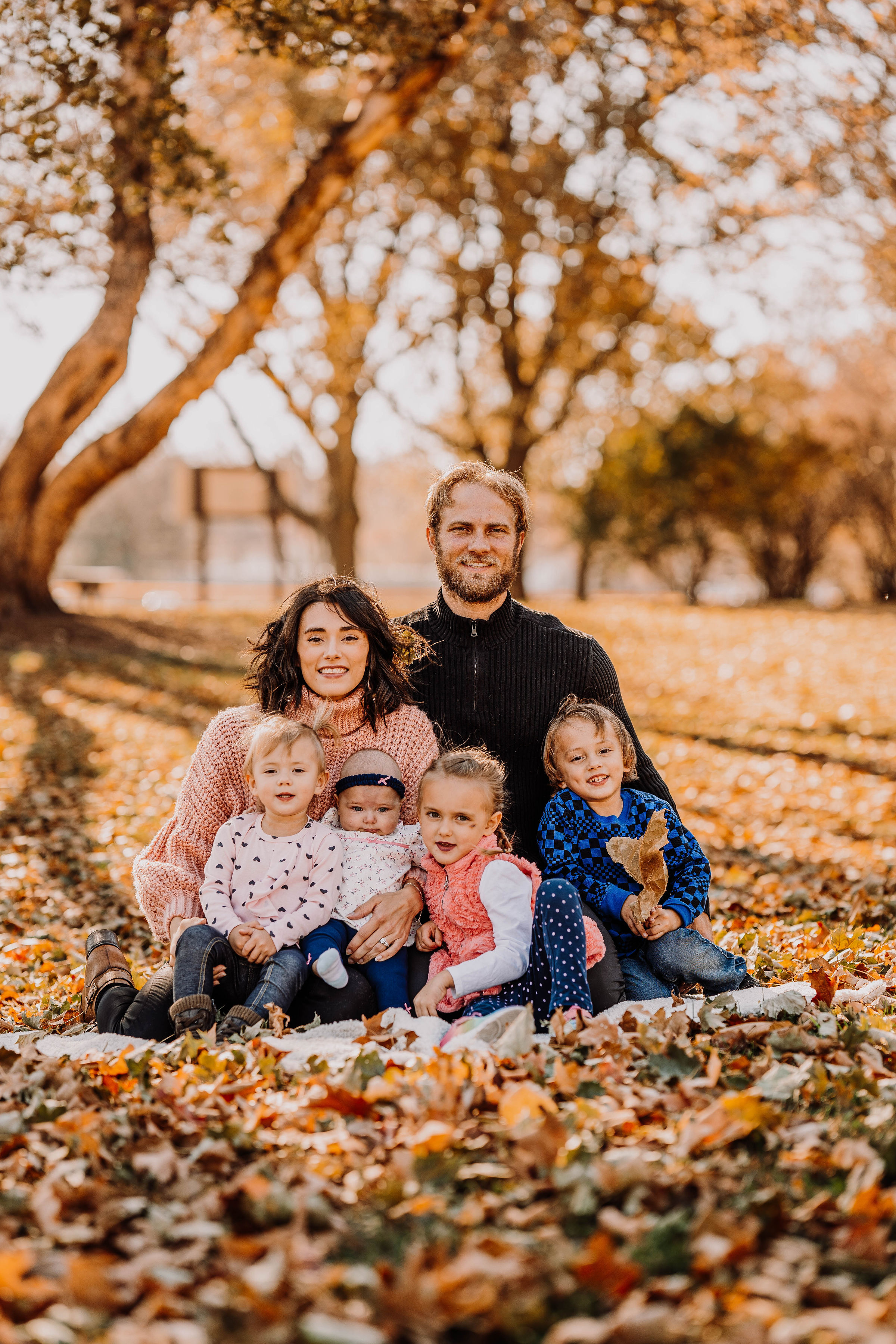 Pastor Kelly and Eli Nelson smiling with their four children outside in a park in omaha
