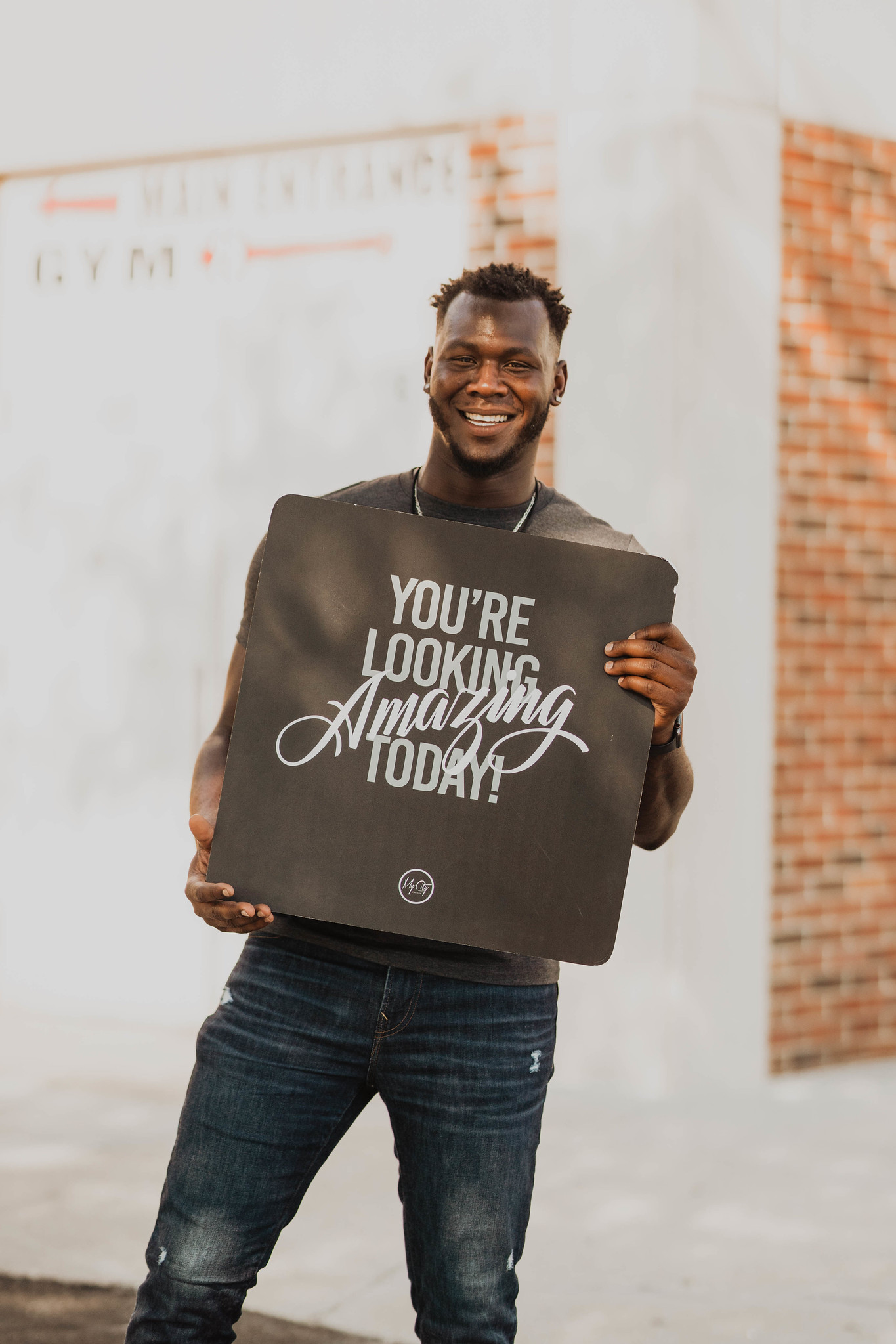 "a young man smiling outside holding a sign that says, ""you look amazing today!"" at a non denominational church in omaha"